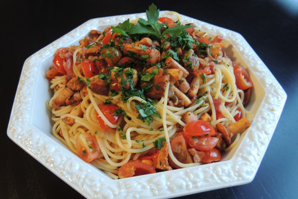 Spaghetti with chanterelles, cherry tomatoes, bacon and parsley